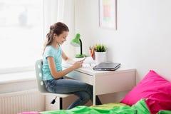 Muchacha con el ordenador portátil y smartphone que manda un SMS en casa Fotografía de archivo libre de regalías
