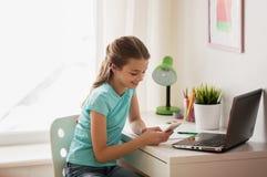 Muchacha con el ordenador portátil y smartphone que manda un SMS en casa Imagen de archivo