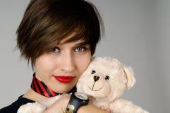 Muchacha con el oso de peluche divertido Imagen de archivo
