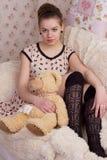 Muchacha con el oso de peluche en cama Foto de archivo