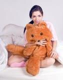 Muchacha con el oso de peluche en cama Fotografía de archivo