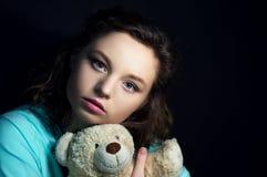 Muchacha con el oso de peluche en la oscuridad Fotos de archivo