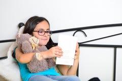 Muchacha con el oso de peluche que lee un libro Fotos de archivo libres de regalías