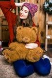 Muchacha con el oso en su mano que se sienta en el cuarto con las paredes de madera Fotografía de archivo