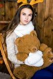 Muchacha con el oso en su mano que se sienta en el cuarto con las paredes de madera Fotos de archivo