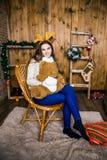Muchacha con el oso en su mano que se sienta en el cuarto con las paredes de madera Imagenes de archivo