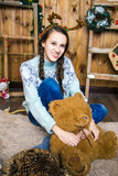 Muchacha con el oso en su mano que se sienta en el cuarto con las paredes de madera Foto de archivo libre de regalías