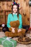 Muchacha con el oso en su mano que se sienta en el cuarto con las paredes de madera Imagen de archivo