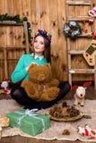 Muchacha con el oso en su mano que se sienta en el cuarto con las paredes de madera Fotos de archivo libres de regalías