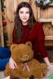 Muchacha con el oso en su mano que se sienta en el cuarto con las paredes de madera Imagen de archivo libre de regalías