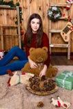 Muchacha con el oso en su mano que se sienta en el cuarto con las paredes de madera Imágenes de archivo libres de regalías