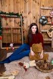 Muchacha con el oso en su mano que se sienta en el cuarto con las paredes de madera Foto de archivo