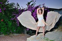Muchacha con el paño del vuelo cerca de las lilas Imagen de archivo libre de regalías