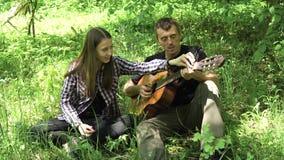 Muchacha con el padre que toca la guitarra almacen de metraje de vídeo