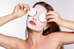 Muchacha con el paquete de cara blanco y cojines de algodón en manos Imagenes de archivo