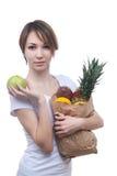 Muchacha con el paquete de frutas y de manzana verde Fotos de archivo libres de regalías