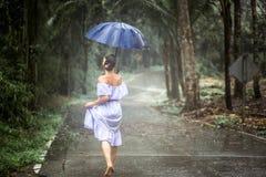 Muchacha con el paraguas debajo de la lluvia Foto de archivo libre de regalías