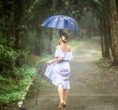 Muchacha con el paraguas debajo de la lluvia Imagenes de archivo