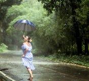 Muchacha con el paraguas debajo de la lluvia Foto de archivo