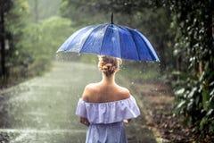 Muchacha con el paraguas debajo de la lluvia Fotografía de archivo