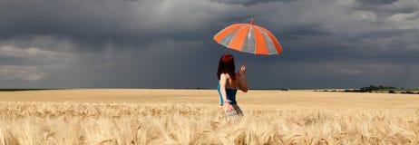 Muchacha con el paraguas en el campo. Imágenes de archivo libres de regalías