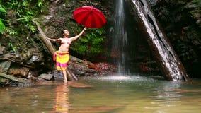 Muchacha con el paraguas en la cascada en la selva tropical de Borneo almacen de metraje de vídeo