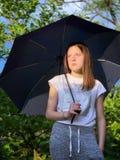 Muchacha con el paraguas en un d?a lluvioso fotografía de archivo