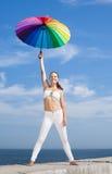 Muchacha con el paraguas iridiscente en el fondo del cielo Imagenes de archivo