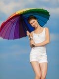 Muchacha con el paraguas iridiscente que mira la cámara en fondo de Foto de archivo