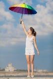 Muchacha con el paraguas iridiscente que mira para arriba en el fondo del cielo Fotografía de archivo