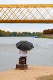 Muchacha con el paraguas que se sienta en la columna del muelle Imagenes de archivo