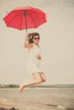 Muchacha con el paraguas rojo en la playa Imagen de archivo libre de regalías