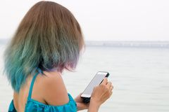 Muchacha con el pelo coloreado que mira en el smartphone fotos de archivo libres de regalías