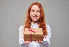 Muchacha con el pelo del tonelero que ofrece una actual caja atada con Imágenes de archivo libres de regalías