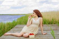 Muchacha con el pelo largo en agua en verano con las fresas Fotografía de archivo libre de regalías