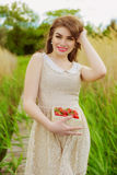 Muchacha con el pelo largo en agua en verano con las fresas Imagen de archivo libre de regalías