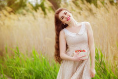 Muchacha con el pelo largo en agua en verano con las fresas Imagenes de archivo