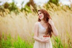 Muchacha con el pelo largo en agua en verano con las fresas Imágenes de archivo libres de regalías