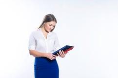 Muchacha con el pelo largo en la ropa de la oficina que mira el doblez de la oficina Fotografía de archivo