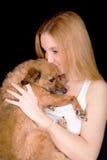 Muchacha con el pelo largo que besa el perro Fotos de archivo