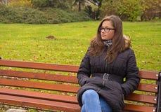 Muchacha con el pelo largo que se sienta en banco Fotografía de archivo
