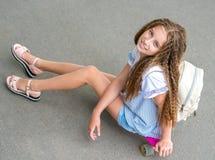 Muchacha con el pelo largo que se sienta en tablero patinador Fotos de archivo