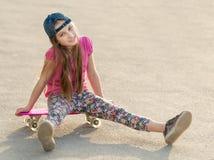 Muchacha con el pelo largo que se sienta en tablero patinador Foto de archivo