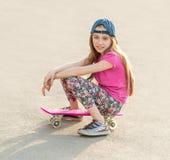 Muchacha con el pelo largo que se sienta en tablero patinador Fotografía de archivo