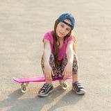 Muchacha con el pelo largo que se sienta en tablero patinador Imagen de archivo
