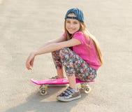 Muchacha con el pelo largo que se sienta en tablero patinador Foto de archivo libre de regalías