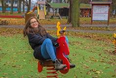 Muchacha con el pelo largo que se sienta en un caballo mecedora Imágenes de archivo libres de regalías