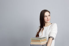 Muchacha con el pelo largo que sostiene una pila de libros y que mira lejos Foto de archivo libre de regalías