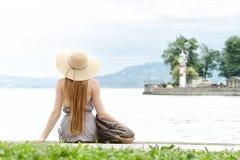Muchacha con el pelo largo y un sombrero que se sienta en el embarcadero con una mochila Faro en la distancia Imagenes de archivo