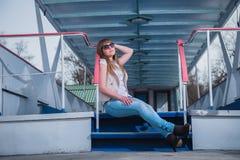 Muchacha con el pelo ligero que se sienta en las escaleras, primavera, día caliente soleado, en gafas de sol y tejanos reclinació Foto de archivo libre de regalías